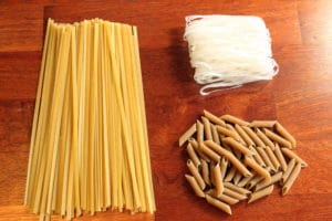 3 different Dry Pastas on Red Wood Background.