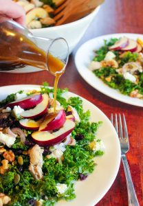 Maple Balsamic Dressing Poured Over Healthy Salad Topped with Sliced Apple.