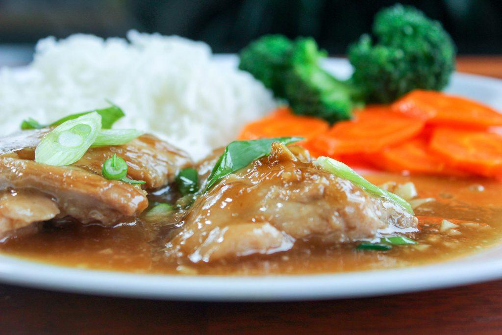 Brown Sugar Garlic Chicken topped with Green Onion, Rice, Broccoli and Carrots in White Plate.