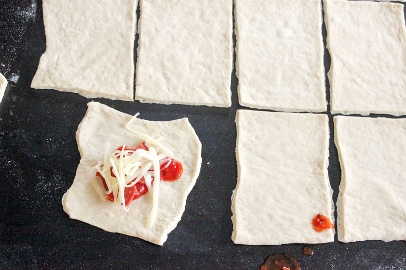 Pizza Pocket Dough Cut into Squares filled with Pizza Sauce and Cheese.