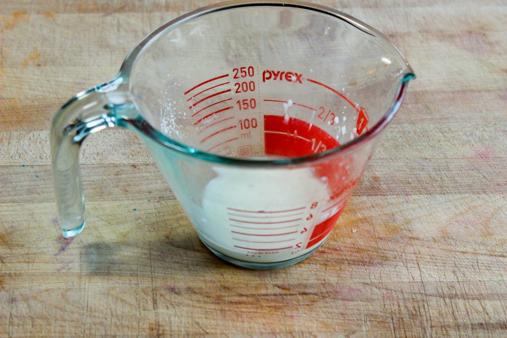 Cornstarch and water mixture in glass measuring cup.