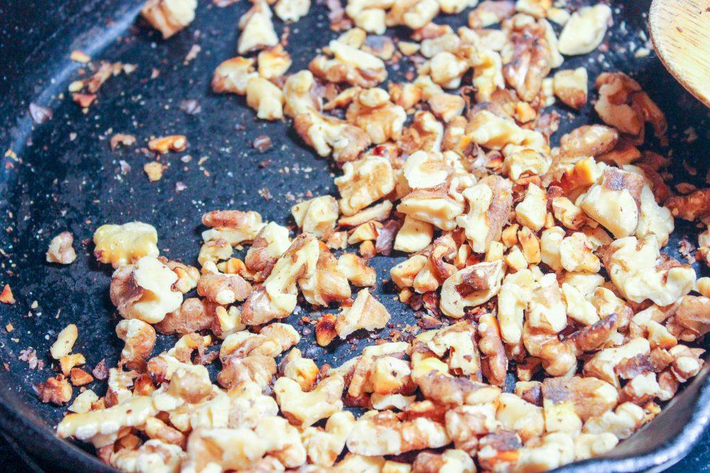 Walnuts toasting inside cast iron frying pan.