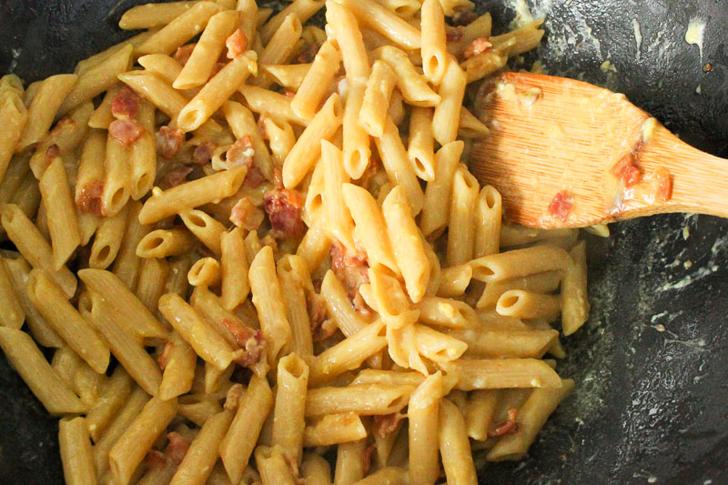 Pasta Carbonara and Bacon mixed in wok.