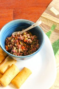 Olive tapenade in blue bowl with crackers on the side.