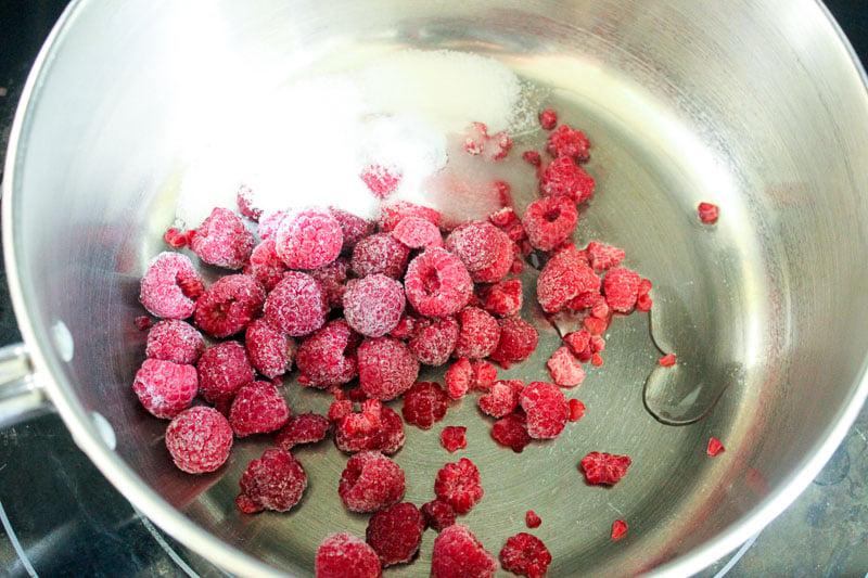 Raspberries and sugar in metal pot on stove.