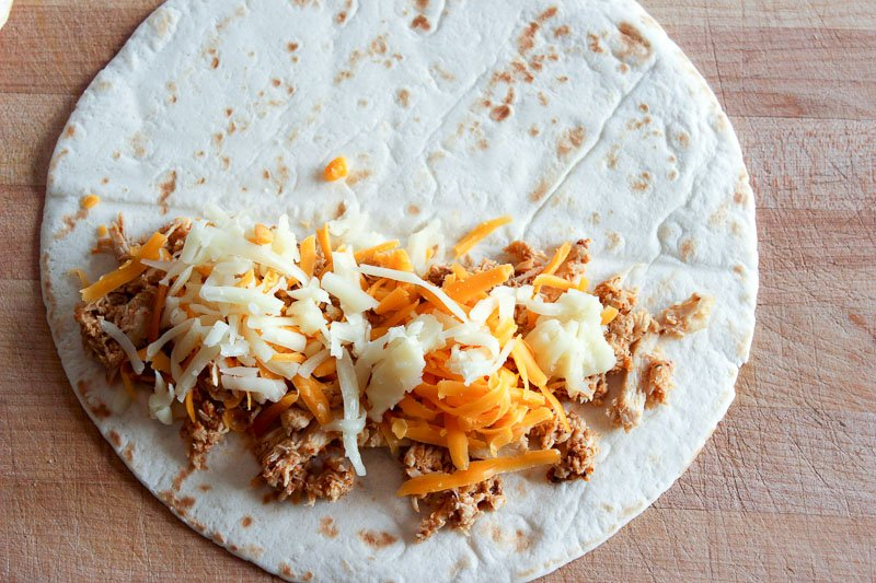 Chicken and shredded cheese on white tortilla on a wood background.