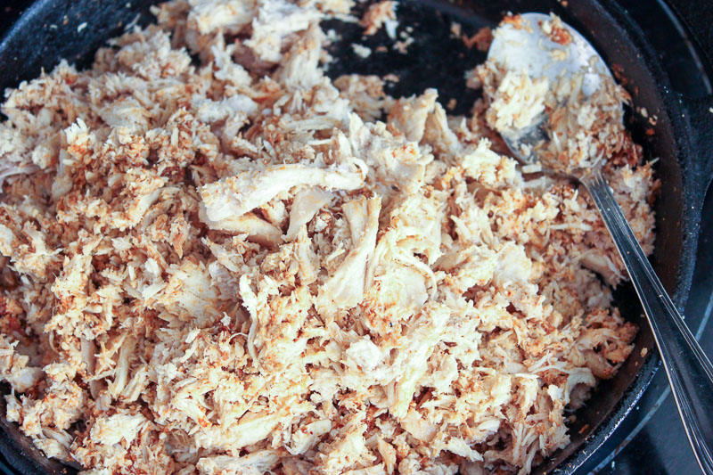 Shredded chicken frying in a cast iron pan.