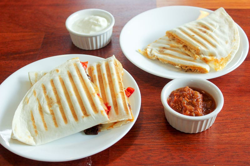 Quesadillas on 2 small white plates with sour cream and salsa in small white cups on a red wood background.