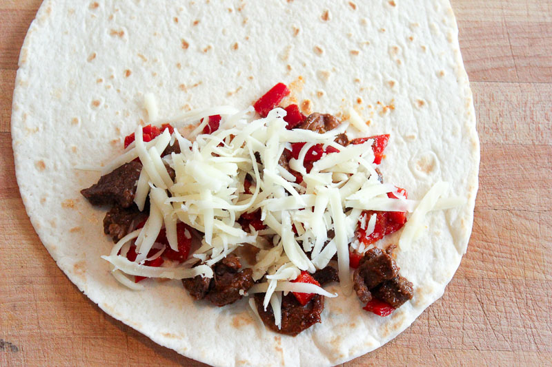 Beef, peppers and shredded cheese on a white tortilla on wood background.
