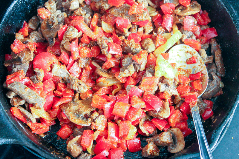 Beef and peppers frying in a cast iron pan.