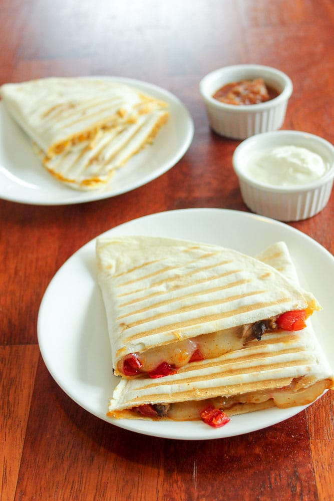 Quesadillas on small white plates, with sour cream and salsa in small white cups on red wood background.