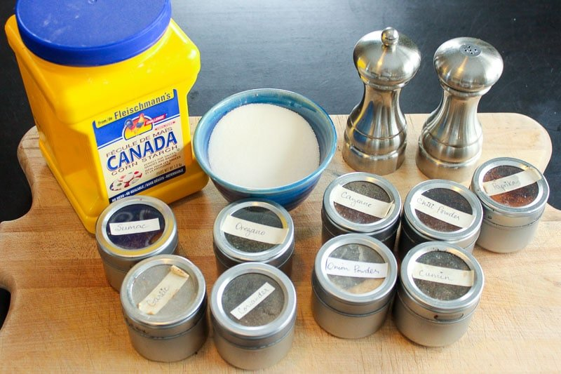 9 metal spice tins, jar of cornstarch, spices in blue bowl and metal salt and pepper shakers on wood board.