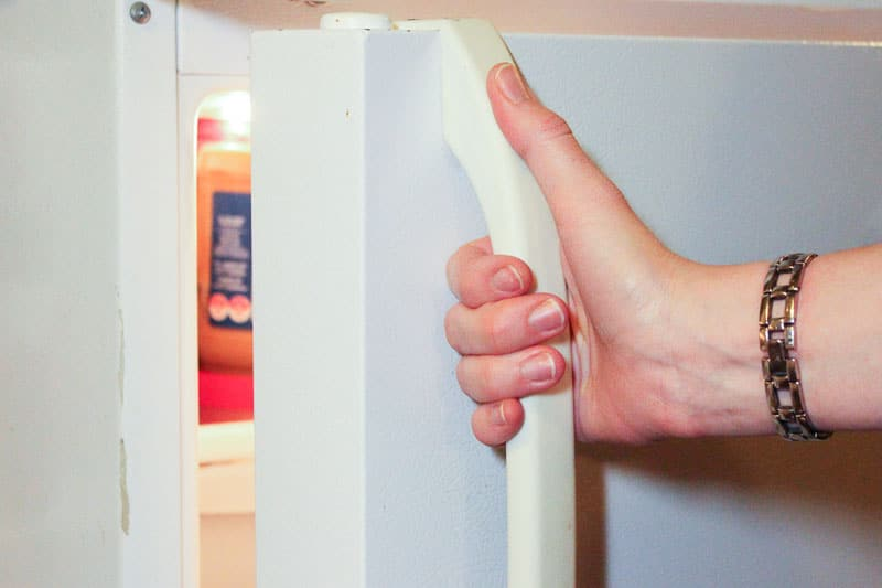 Opening a White Refrigerator Door.