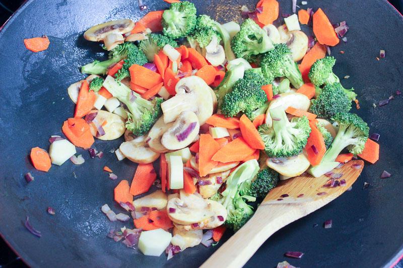 Vegetables frying in wok.