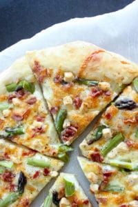 Sliced Asparagus Bacon Goat Cheese Pizza on Parchment Paper.