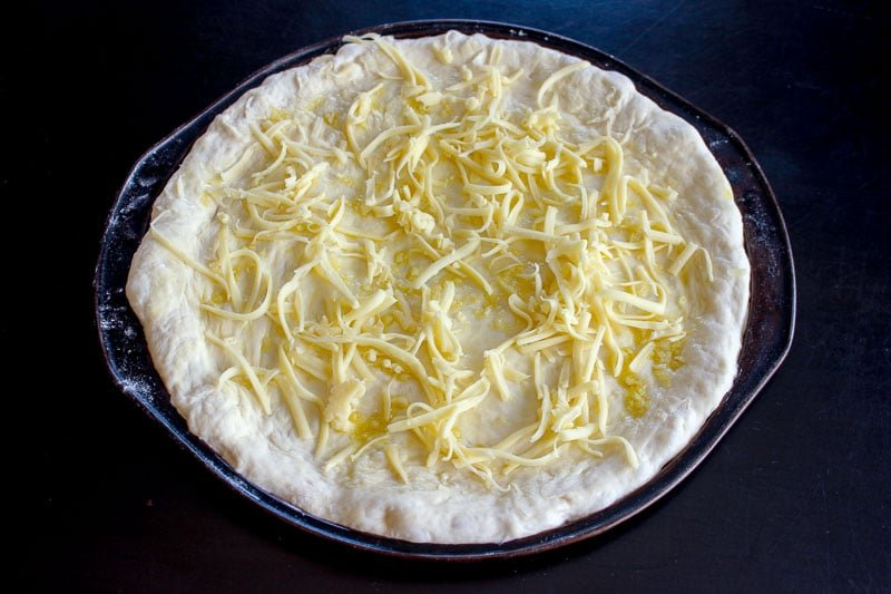 Shredded Mozzarella Cheese on Round Pizza Dough.