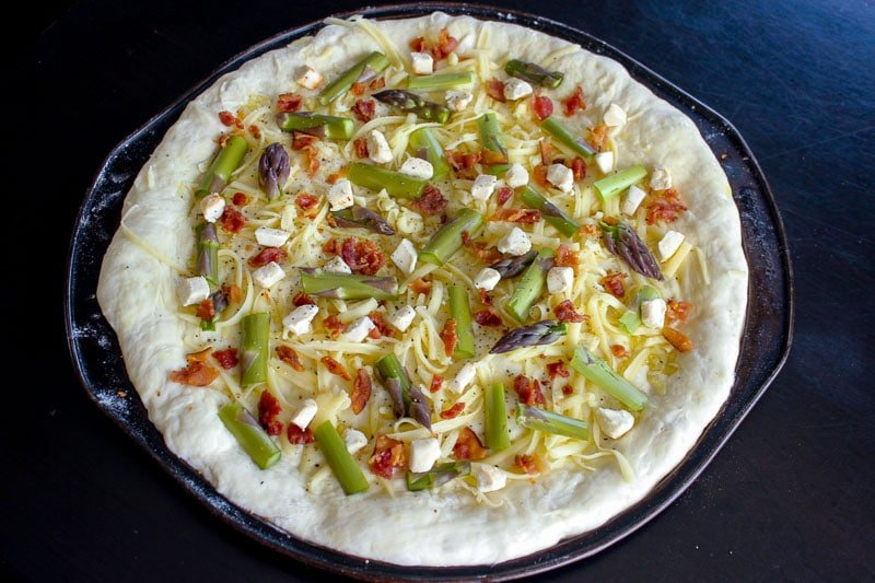 Bacon, goat cheese and asparagus on top of round pizza dough.