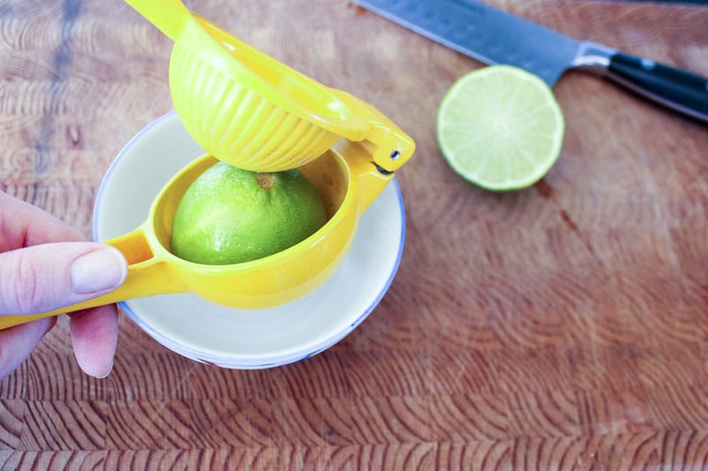 Lime in yellow citrus juicer.