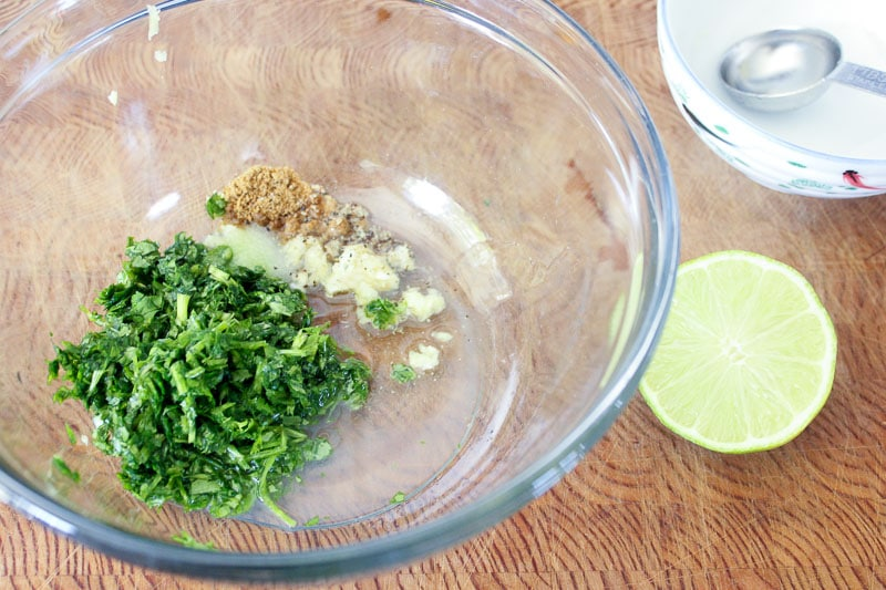 Chopped cilantro, garlic and cumin in glass mixing bowl.