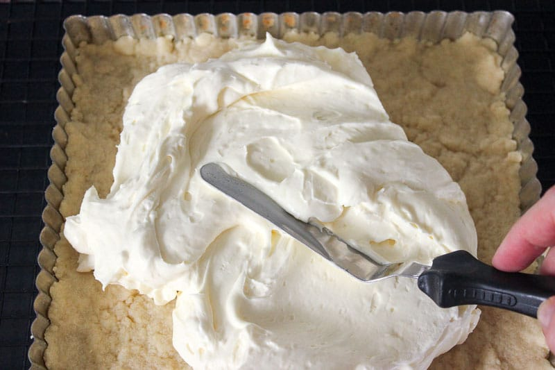 Spreading cream cheese on top of Shortbread crust in square tart pan.