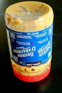 Upside down empty jar of natural peanut on black background.