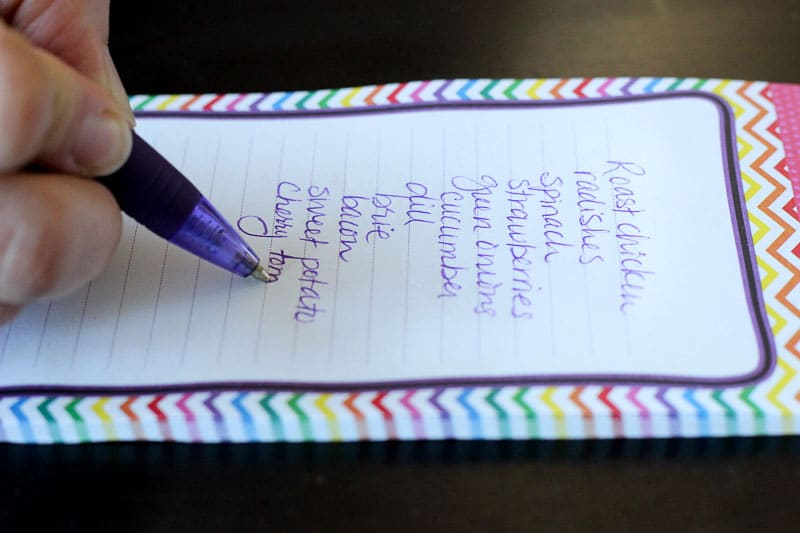 Grocery list written on note pad.