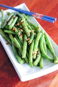 Asian-Style Green Beans and Blue Chopsticks on White Plate.