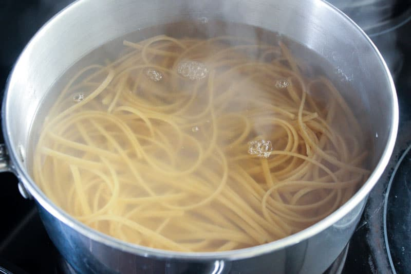 Pasta in water in a metal pot on stove.