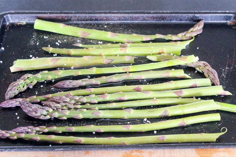 Kosher salt on asparagus stalks on metal sheet pan.