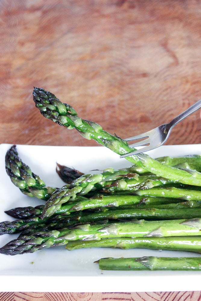 Roasted Asparagus Spears on White Plate.