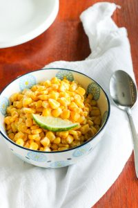 Mexican Corn Topped with Lime Wedge in White and Blue Bowl.