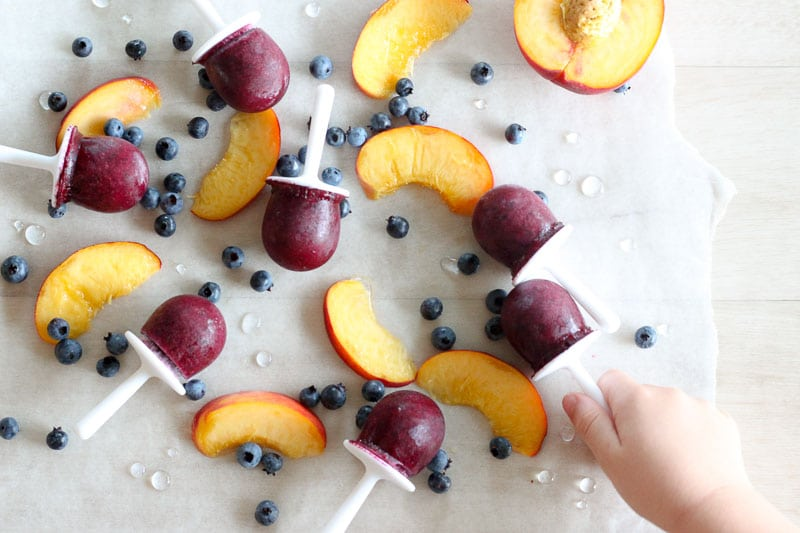 Blueberry Peach Popsicles surrounded by blueberries and sliced peaches on parchment paper.