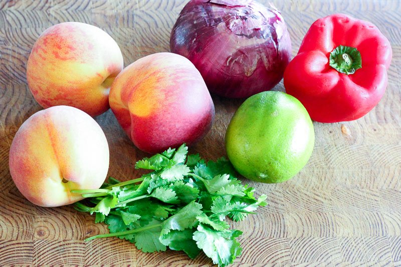 Peaches, Red Onion, Red Pepper, Lime and Cilantro on Wooden Board.