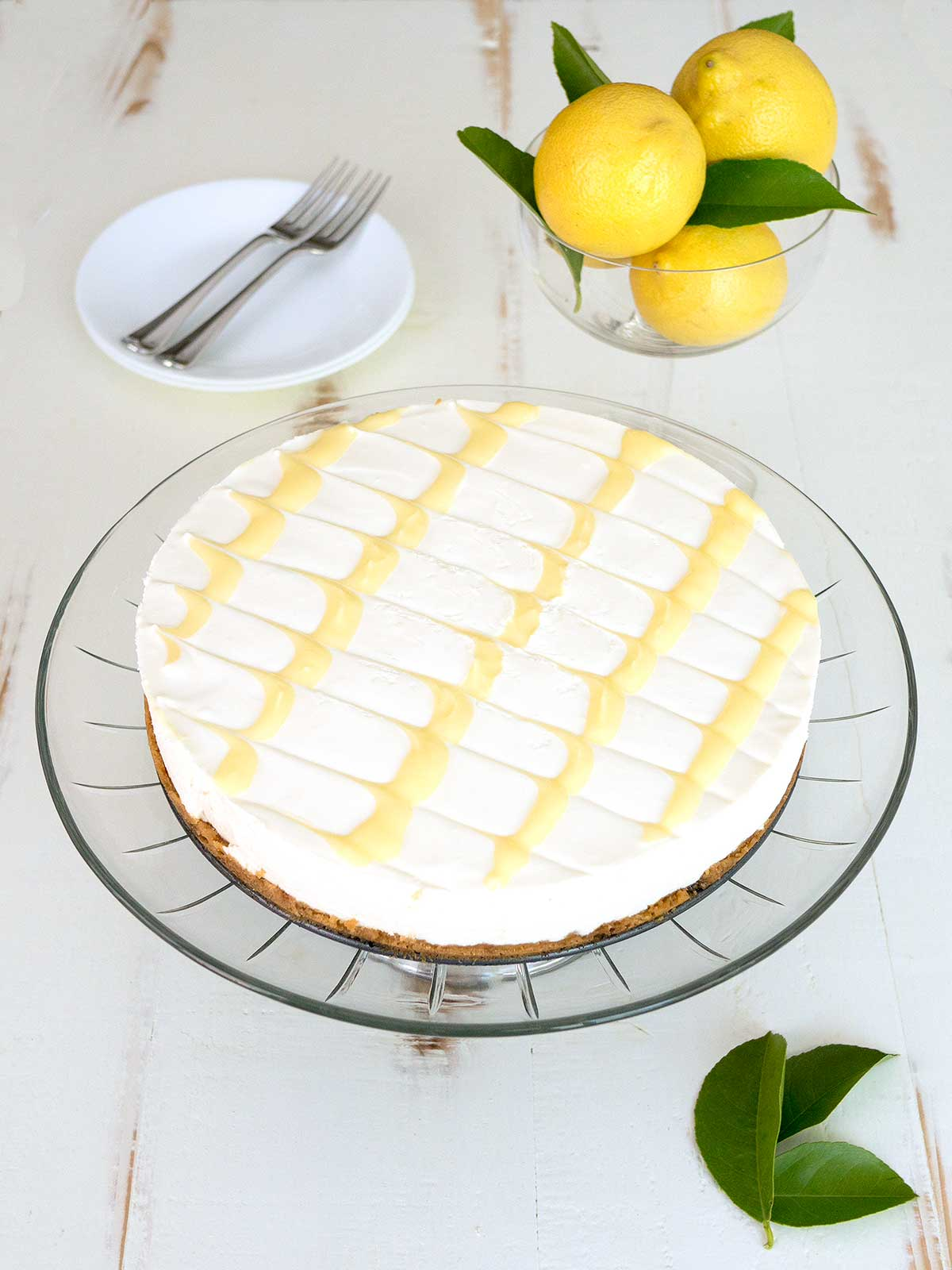 Cheesecake Topped with Lemon Curd on Glass Plate.