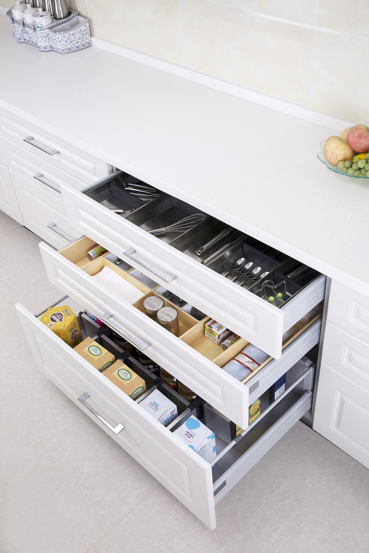White Drawers filled with Kitchen Utensils.