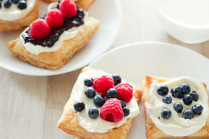 Cream Cheese Pastries topped with Blueberries and Raspberries on White Plates.