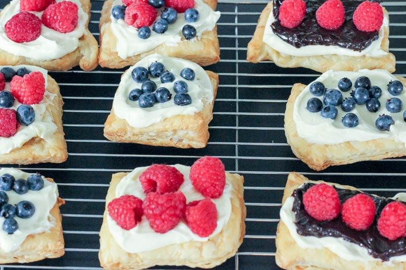Cream Cheese Pastries topped with Blueberries and Raspberries on Wire Rack.