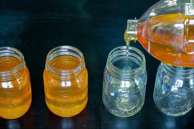 Pouring Honey into Glass Mason Jars.