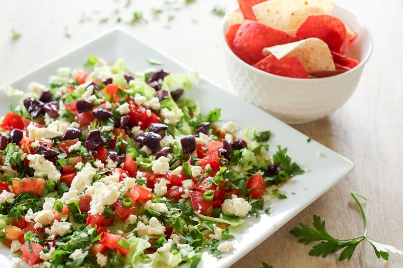 Mediterranean Dip on White Square Dish with Bowl of Red and White Nacho Chips.