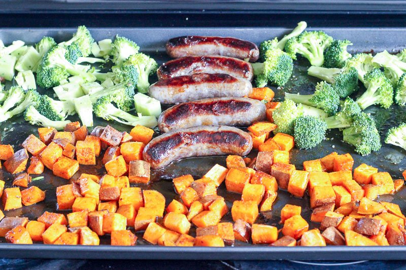 Chopped Broccoli, Cubed Sweet Potatoes and Sausages on Sheet Pan.