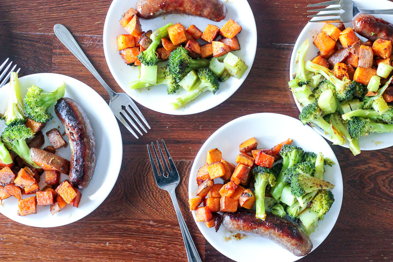 Sausage, Cubed Sweet Potatoes and Chopped Broccoli on white plates.