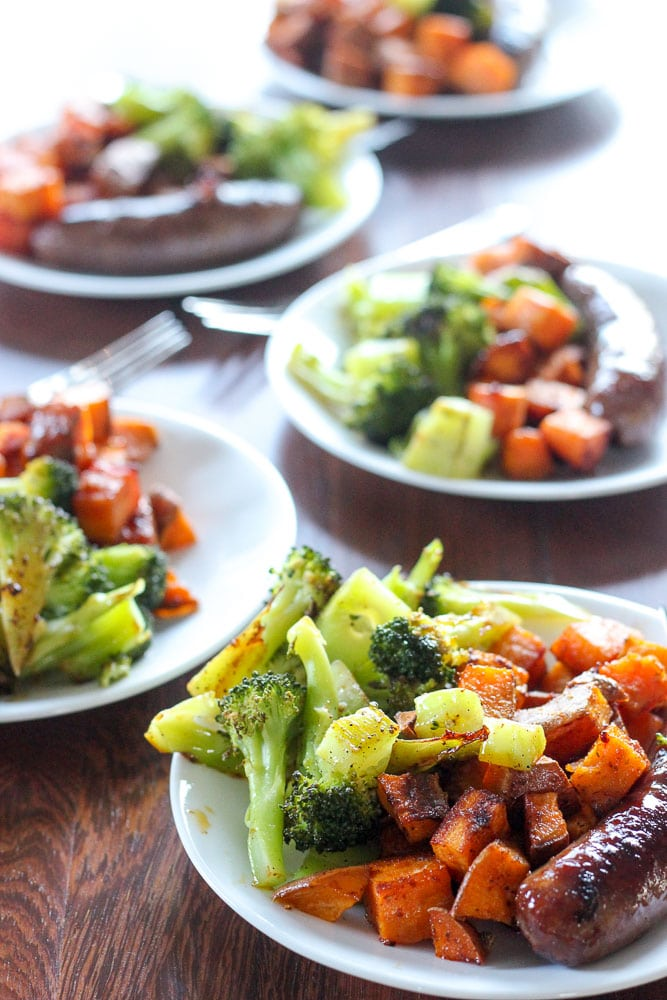 Sausages, Cajun Sweet Potatoes and Chopped Broccoli on White Plates.