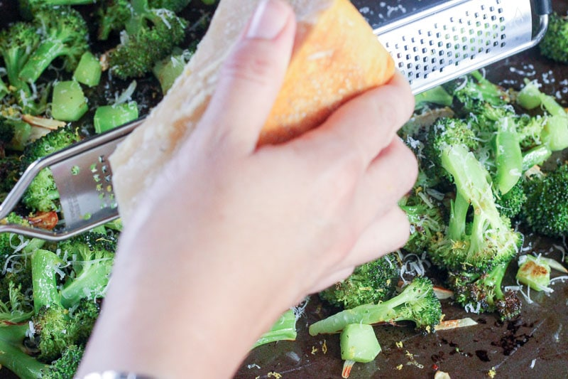 Grating Fresh Parmesan onto Oven Roasted Broccoli.