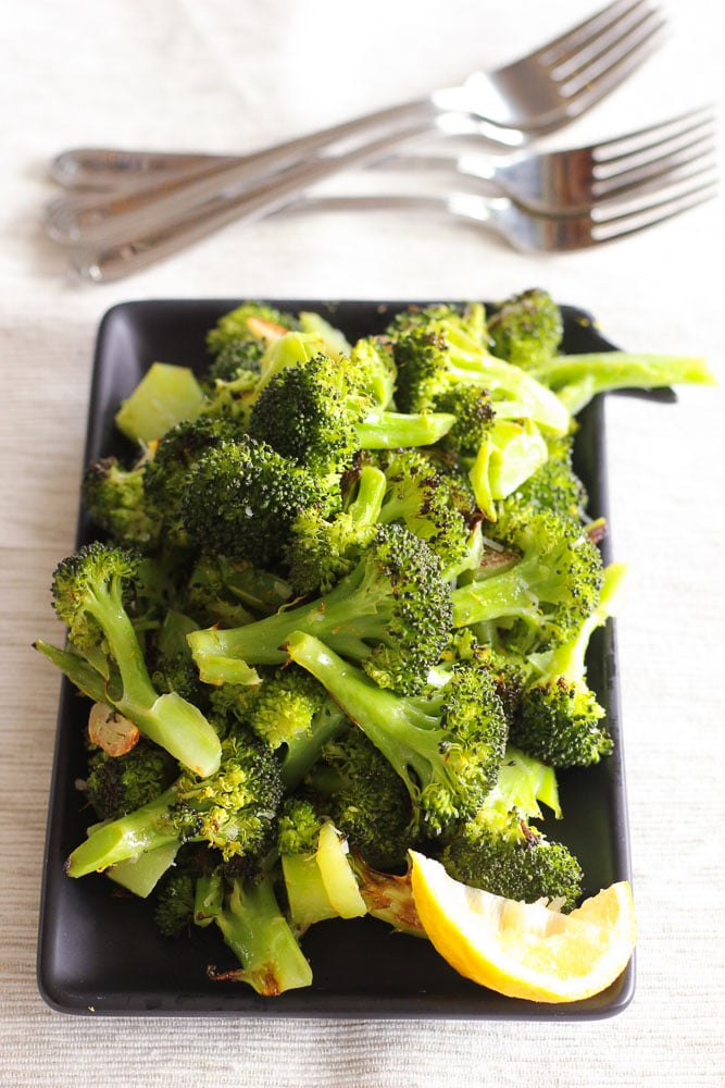 Oven Roasted Broccoli and Lemon Wedge on Black Plate.