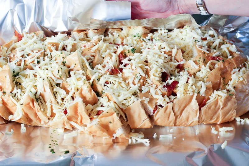 Sliced Loaf of Bread topped with Bacon and Shredded Mozzarella Cheese.