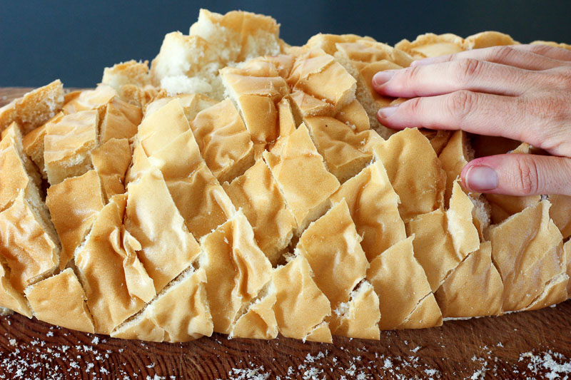 Hand on Top of Sliced Loaf of Bread.