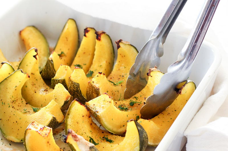 Oven Baked Maple Squash topped with Parsley and pepper in white bowl.