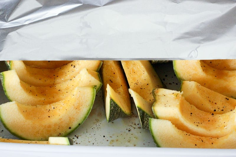 Covering Sliced Squash with Aluminum Foil.