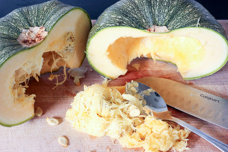 Removing Seeds from Squash on Wooden Board.