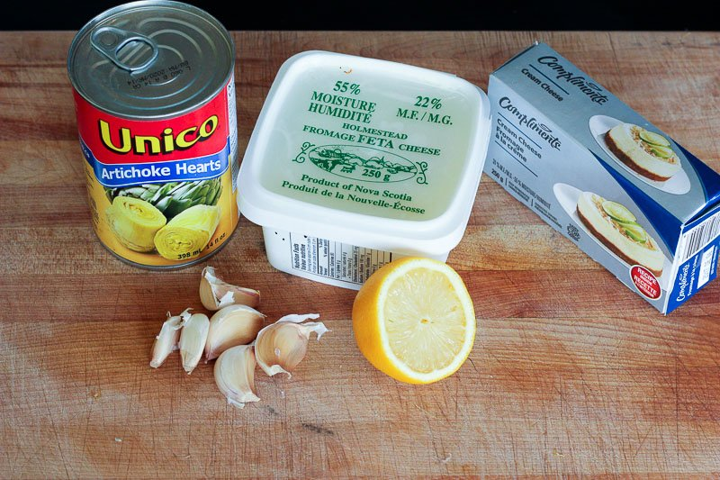 Ingredients for Whipped Artichoke and Feta Dip - canned artichoke hearts, feta cheese, cream cheese, lemon and fresh garlic.